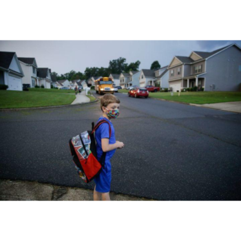 Young boy wearing a backpack and mask stands on the sidewalk of a suburban street.