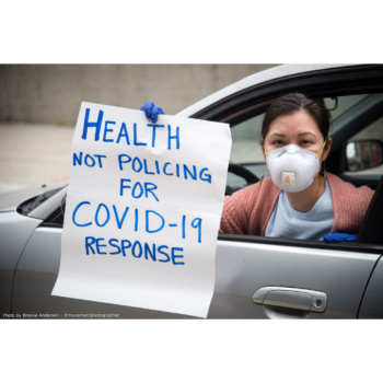 "Amber Akemi Piatt wearing a mask, and holding a sign that reads ""Health not policing for COVID-19 response"" out the window of her car (from a recent car caravan protest in support of the Movement for Black Lives)"