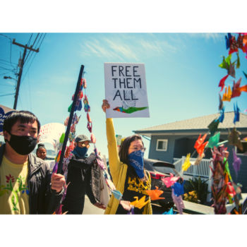 "Photo of organizers marching in front of San Quentin to demand that CA #FreeThemAll. Amber is pictured at center, wearing a mask and holding up a sign that reads ""FREE THEM ALL"""