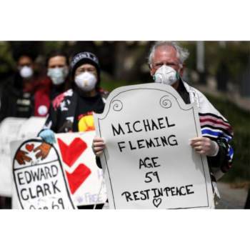 "Faith leaders, activists and family members hold a public memorial in front of the Phillip Burton Federal Building and U.S. Courthouse in San Francisco to honor 17 people who died of COVID-19 while in prison or ICE detention; person in the foreground is pictured wearing a white mask, holding a sign that reads ""Michael Fleming Age 59 Rest In Peace"""