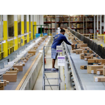 photo of a worker standing on a step-stool in an Amazon warehouse isle, leaning over to place boxes on a conveyor belt