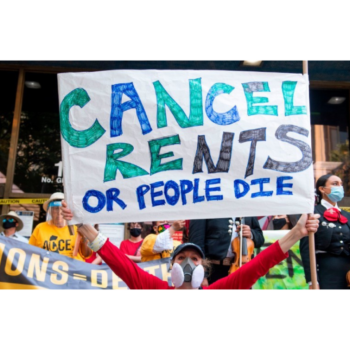 "Photograph of a person wearing a mask, standing amidst a crowd outside, holding a large sign over their head that reads ""CANCEL RENTS OR PEOPLE DIE"""