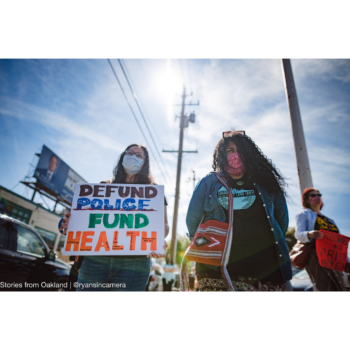 """Photo of two protestors in Oakland outside on a sunny day. Both wear masks, the person at left holds a sign that reads """"DEFUND POLICE FUND HEALTH"""""""