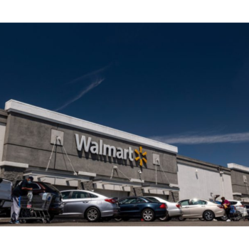 Photo of the exterior of a Walmart store shows a crowded parking lot