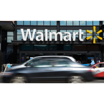 Photo of a car in motion driving past a building with a large Walmart sign and logo on it