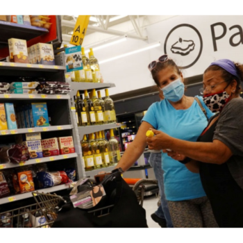 Two people wearing protective masks while looking at a wine bottle, shopping in a Walmart store on May 18, 2021 in Hallandale Beach, Florida.