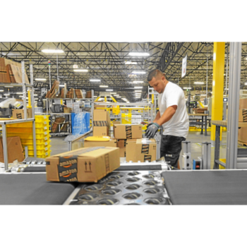 Photo of a person working at an Amazon warehouse, unloading boxes from a conveyor belt onto shelving.