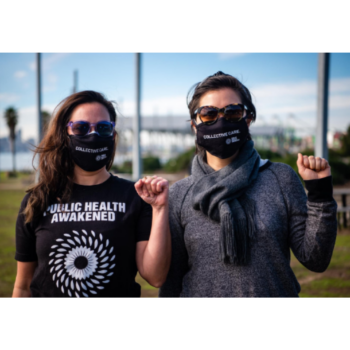 """Photograph of two public health pracitioners, both wearing masks and holding raised fists, wearing Public Health Awakened t-shirt and mask that reads """"Collective Care"""""""