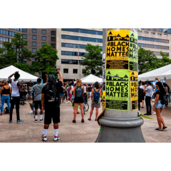 """Photo of a group of people outside in a plaza; in the foreground a telephone pole is covered in flyers reading """"Black Homes Matter"""""""